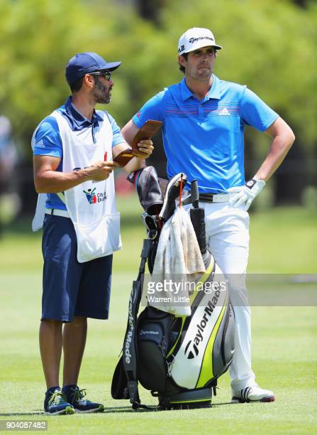 Nacho Elvira of Spain talks with his caddie Diego Suazo as he prepares to play his second shot on the 4th hole during day two of the BMW South...