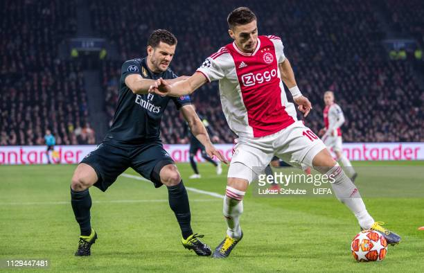Nacho Fernandez of Madrid challenges for the ball with Dusan Tadic of Amsterdam during the UEFA Champions League Round of 16 First Leg match between...