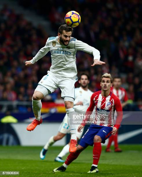 Nacho Fernandez of Real Madrid CF saves on a header ahead Antoine Griezmann of Atletico de Madrid during the La Liga match between Club Atletico...