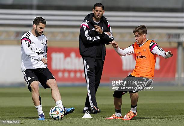 Nacho Fernandez of Real Madrid competes for the ball with Alvaro Jimenez of Real Madrid Academy as assistant coach Fernando Hierro gives instructions...