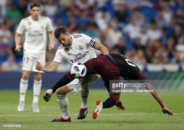 Nacho Fernandez of Real Madrid competes for the ball with Carlos Bacca of AC Milan during the Trofeo Santiago Bernabeu match between Real Madrid and...