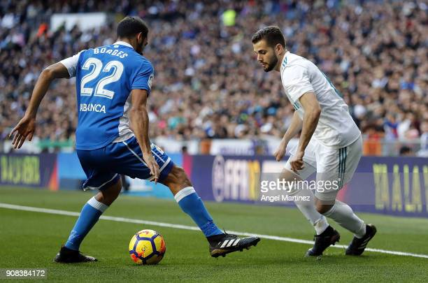 Nacho Fernandez of Real Madrid competes for the ball with Celso Borges of Deportivo during the La Liga match between Real Madrid and Deportivo La...