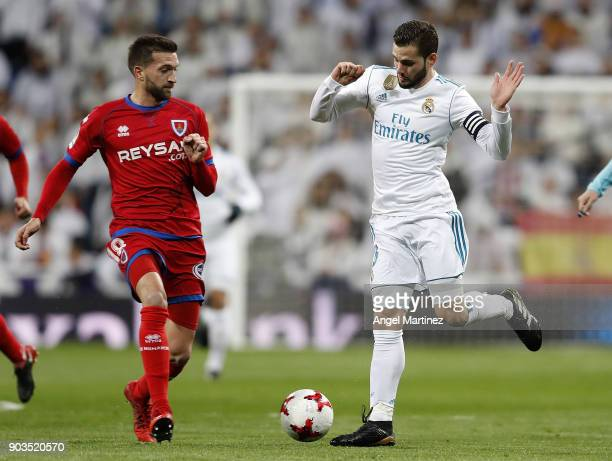 Nacho Fernandez of Real Madrid competes for the ball with Gregorio Sierra of Numancia during the Copa del Rey round of 16 second leg match between...