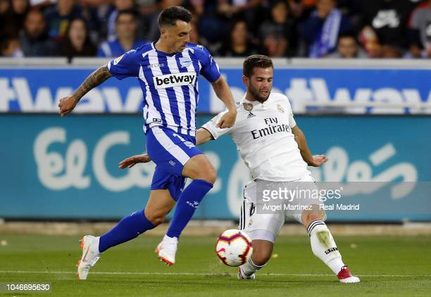 Nacho Fernandez of Real Madrid competes for the ball with Ximo Navarro of Deportivo Alaves during the La Liga match between Deportivo Alaves and Real...
