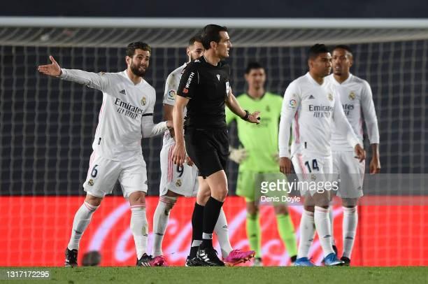 Nacho Fernandez of Real Madrid interact with Referee Juan Martinez Munuera after he awarded a penalty kick to Sevilla FC during the La Liga Santander...