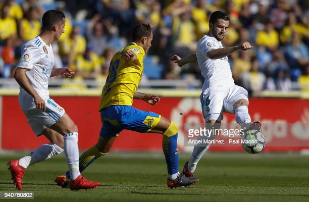 Nacho Fernandez of Real Madrid is challenged by Javi Castellano of UD Las Palmas during the La Liga match between UD Las Palmas and Real Madrid at...