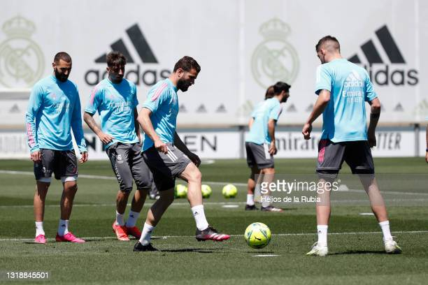 Nacho Fernández and Federico Valverde both of Real Madrid are training with teammate Karim Benzema at Valdebebas training ground on May 19, 2021 in...