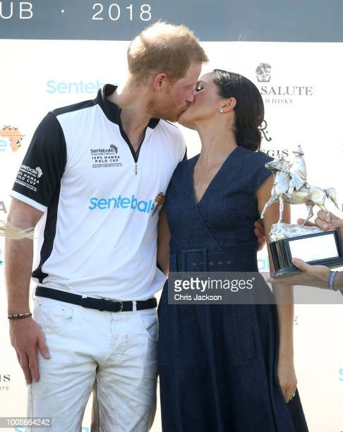 Nacho Figuares of Sentebale St Regis presents the Sentebale Polo 2018 trophy as Meghan Duchess of Sussex and Prince Harry Duke of Sussex kiss after...