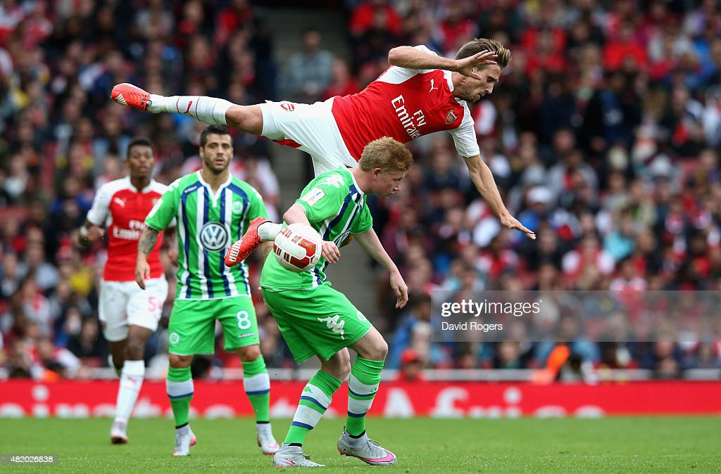 Nacho Monreal of Arsena falls over Kevin de Bruyne during the Emirates Cup match between Arsenal and VfL Wolfsburg at the Emirates Stadium on July 26, 2015 in London, England.