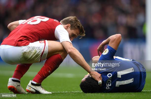 Nacho Monreal of Arsenal checks that Pedro of Chelsea is okay after going down injured during the Premier League match between Chelsea and Arsenal at...