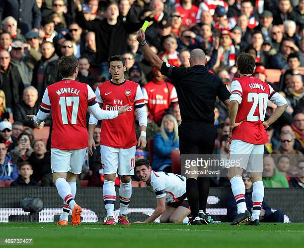 Nacho Monreal of Arsenal gets a yellow card during the FA Cup Fifth Round match between Arsenal and Liverpool at Emirates Stadium on February 16 2014...