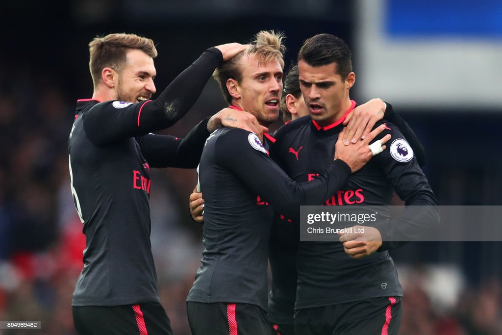 Nacho Monreal (C) of Arsenal is congratulated by team-mates Aaron Ramsey (L) and Granit Xhaka after scoring the equaliser during the Premier League match between Everton and Arsenal at Goodison Park on October 22, 2017 in Liverpool, England.