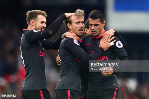 Nacho Monreal of Arsenal is congratulated by teammates Aaron Ramsey and Granit Xhaka after scoring the equaliser during the Premier League match...