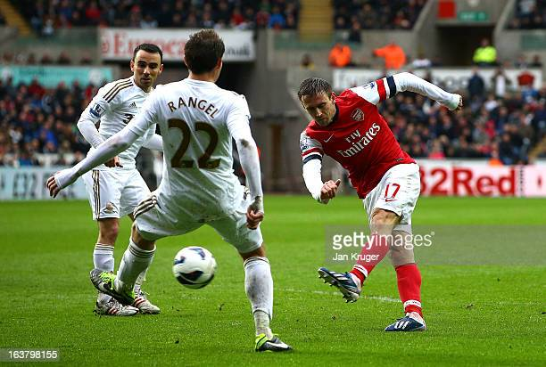 Nacho Monreal of Arsenal shoots past Angel Rangel of Swansea City for their first goal during the Barclays Premier League match between Swansea City...
