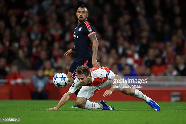 Nacho Monreal of Arsenal stoops to clear the ball as Arturo Vidal of Bayern Munich looks on during the UEFA Champions League Group F match between...