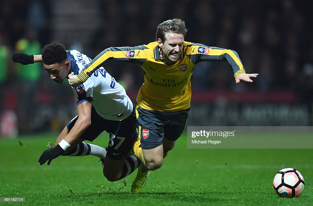 Nacho Monreal of Arsenal tangles with Callum Robinson of Preston North End during the Emirates FA Cup Third Round match between Preston North End and Arsenal at Deepdale on January 7, 2017 in Preston, England.