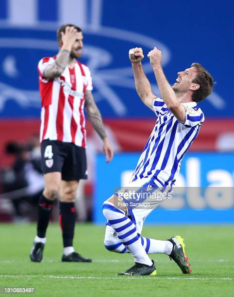 Nacho Monreal of Real Sociedad celebrates their team's victory at full-time as Inigo Martinez of Athletic Bilbao looks dejected after the Copa Del...