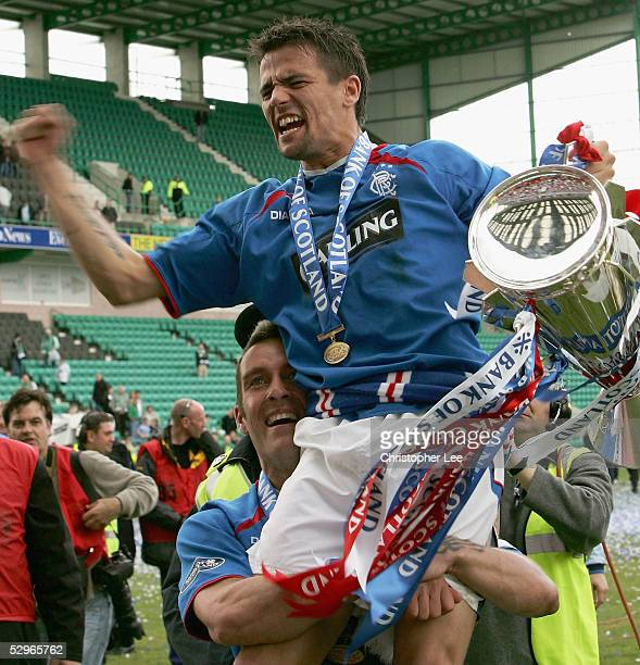 Nacho Novo of Rangers is lifted into the air by his captain Fernando Ricksen as they celebrate with the Scottish Premier League trophy during the...