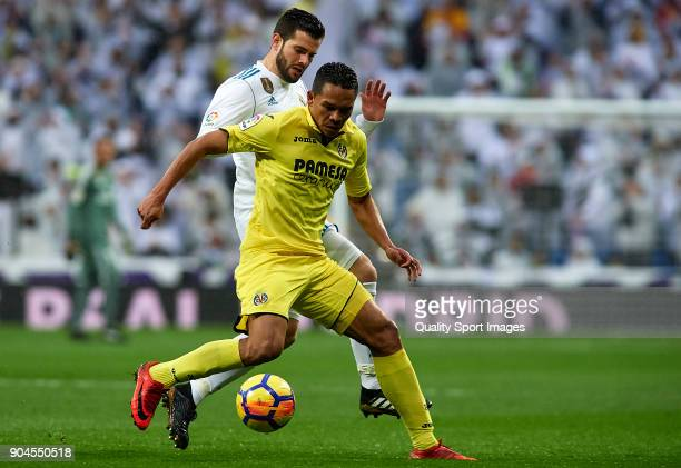Nacho of Real Madrid competes for the ball with Carlos Bacca of Villarreal during the La Liga match between Real Madrid and Villarreal at Estadio...