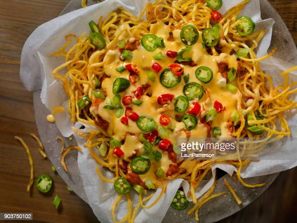 nacho style thin and crispy spiral fries with chili and cheese sauce - cheese sauce stock photos and pictures