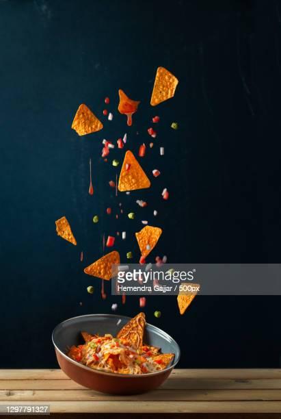 nachos levitating against black background,vadodara,gujarat,india - images stock pictures, royalty-free photos & images