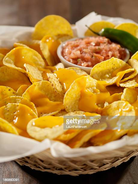 nachos with cheese sauce and salsa - cheese sauce stock photos and pictures