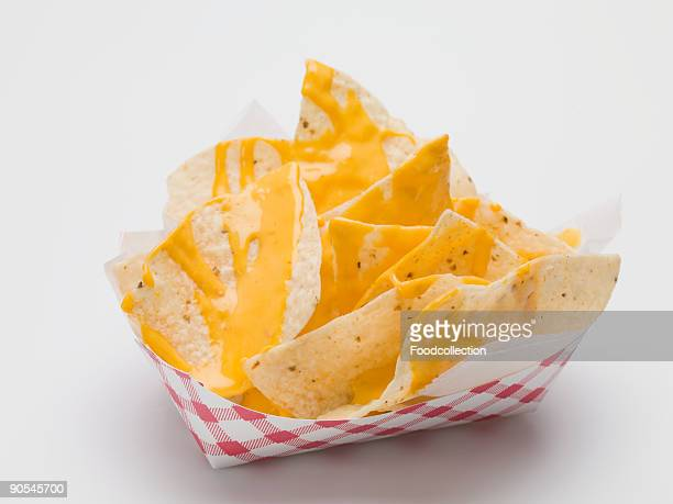 nachos with cheese sauce in paper dish, close up - cheese sauce stock photos and pictures