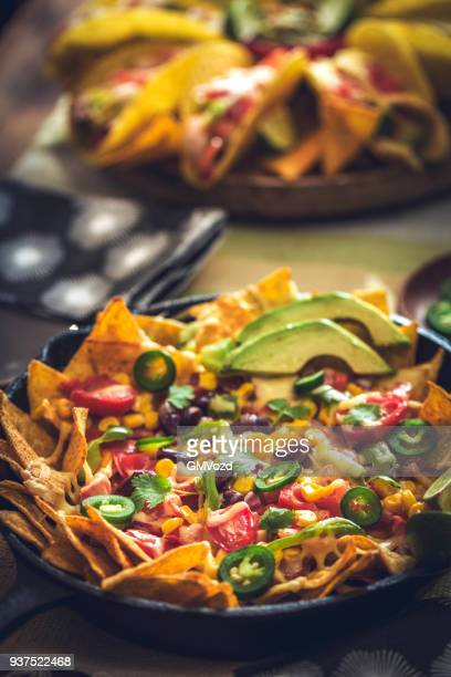nachos with hot salsa and cheese dipping sauce - nachos stock photos and pictures