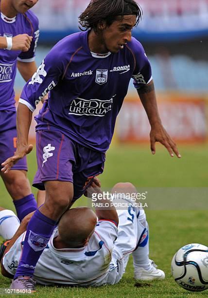 Nacional's player Raul Ferro vies for the ball with Defensor's footballer Damian Suarez during their Uruguayan Apertura tournament football match in...