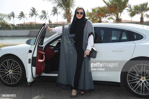 Nada Edlibi poses for a photo next to her husband's Porsche Panamera that she took for a spin on the first day that she is legally allowed to drive...