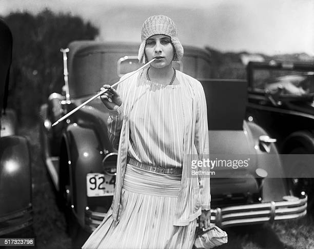 Nadeja De Braganza daughter of Princess Miguel De Braganza smokes a cigarette from a long cigarette holder while standing near parked cars June 15...