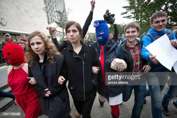 Nadezhda Tolokonnikova Maria Alyokhina and two masked activists of the punk group Pussy Riot arrive for a news conference held outside a hotel in a...