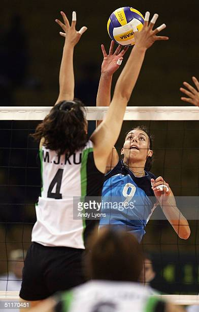 Nadia Centoni of Italy hits the ball while defended by Jung Min Ku of Korea in the women's indoor Volleyball preliminary match on August 14 2004...