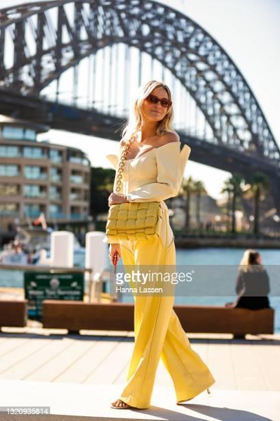 Nadia Fairfax wearing yellow Paris Georgia top and pants, Bottega Veneta bag Banbe sunglasses at Afterpay Australian Fashion Week 2021 on May 31,...