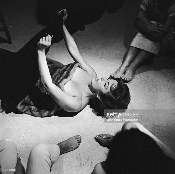 Nadia Gray lies naked on the floor covered in furs in a party scene from 'La Dolce Vita' directed by Federico Fellini