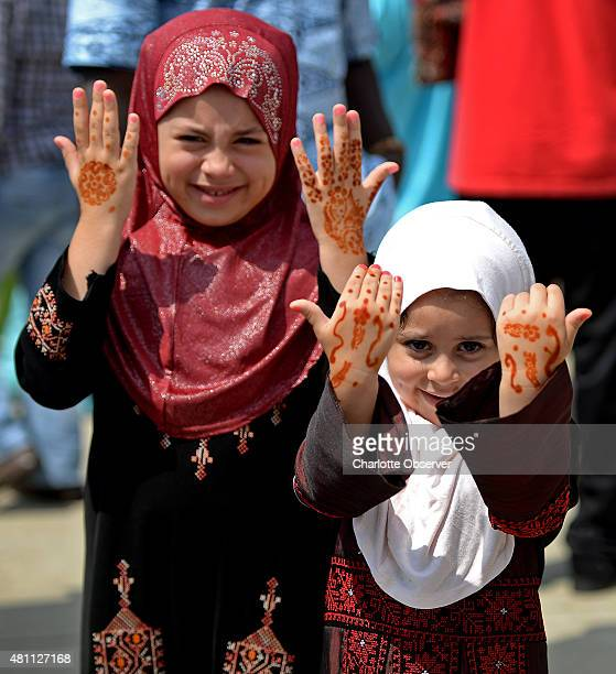 Nadia Mejalli left and her sister Mariam show the henna on their hands as they joined thousands of Charlottearea Muslims gathered to mark the end of...