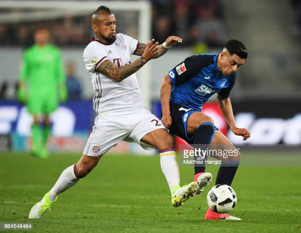 Nadiem Amiri of 1899 Hoffenheim is tackled by Arturo Vidal of Bayern Munich during the Bundesliga match between TSG 1899 Hoffenheim and Bayern...