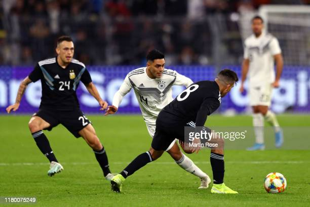 Nadiem Amiri of Germany passes the ball under pressure from Marcos Acuna of Argentina during the International Friendly match between Germany and...