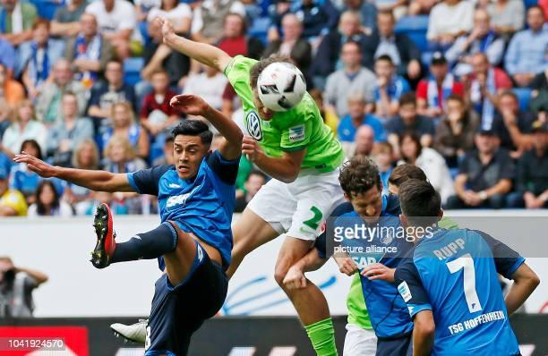 Nadiem Amiri of Hoffenheim and Philipp Wollscheid of Wolfsburg vie for the ball during the German Bundesliga soccer match between 1899 Hoffenheim and...