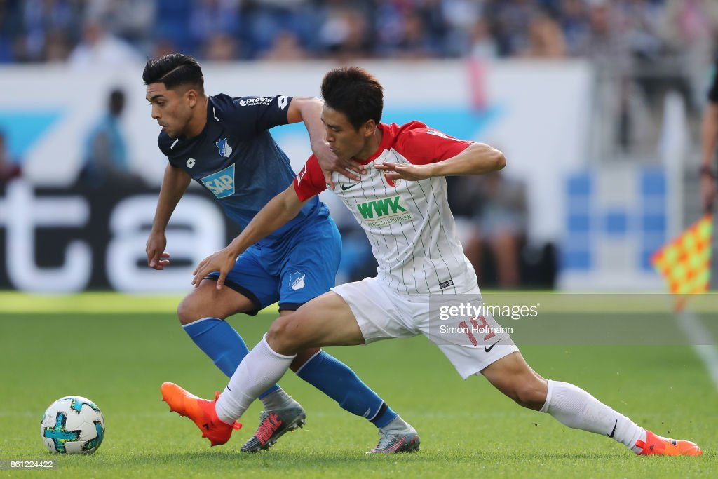 Nadiem Amiri of Hoffenheim (l) fights for the ball with Koo Ja-cheol of Augsburg during the Bundesliga match between TSG 1899 Hoffenheim and FC Augsburg at Wirsol Rhein-Neckar-Arena on October 14, 2017 in Sinsheim, Germany.