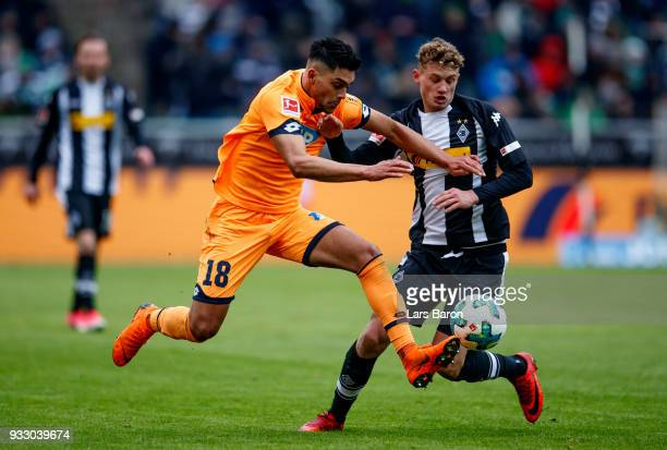 Nadiem Amiri of Hoffenheim is challenged by Mickael Cuisance of Moenchengladbach during the Bundesliga match between Borussia Moenchengladbach and...