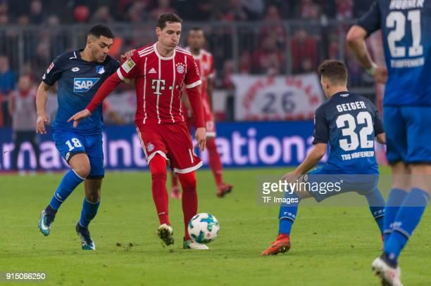 Nadiem Amiri of Hoffenheim Sebastian Rudy of Bayern Muenchen and Dennis Geiger of Hoffenheim battle for the ball during the Bundesliga match between...