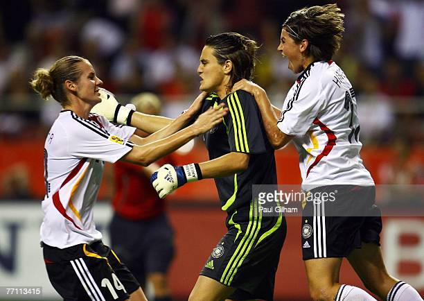 Nadine Angerer of Germany is congratulated by Simone Laudehr and Ariane Hingst after saving a penalty from Marta Vieira Da Silva of Brazil during the...