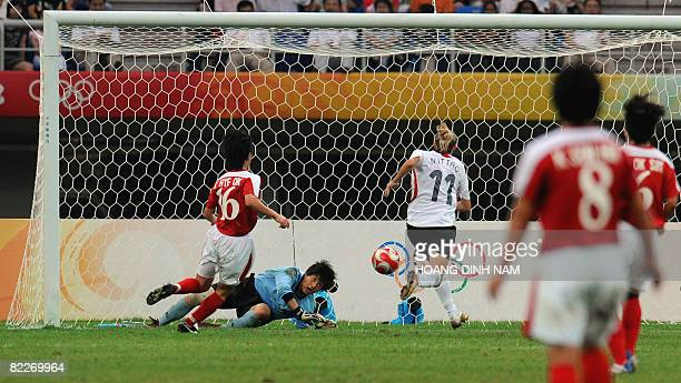 Nadine Angerer of Germany scores a goal as North Korean goalkeeper Jon Myong Hui fails to block during their women's first round group F football...