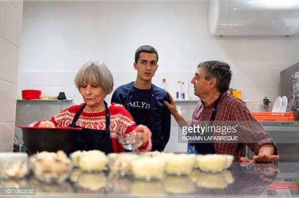 Nadine Octave and LouisMarie prepare a dinner at an 'Escale Solidaire' in the 6th district of Lyon centraleastern France on November 11 2018 The...