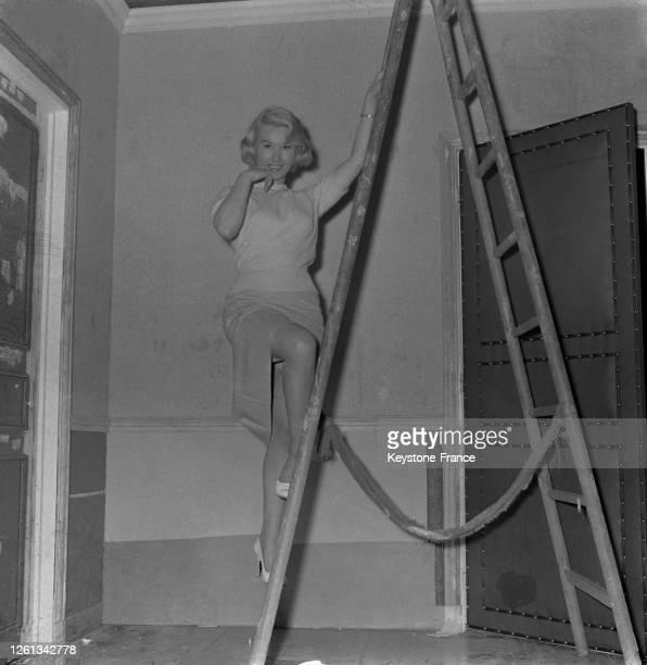 Nadine Tallier, future Nadine de Rothschild, photographiée debout sur une échelle, à Paris, France le 21 avril 1957.