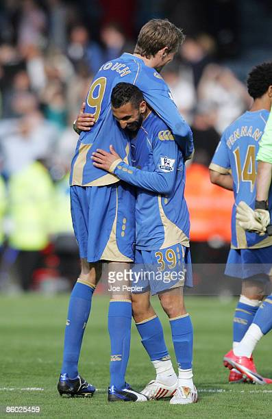 Nadir Belhadj and Peter Crouch of Portsmouth celebrate the win after the Barclays Premier League match between Portsmouth and Bolton Wanderers at...