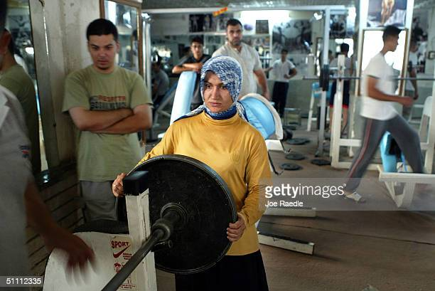 Nadira Hamza puts weights on the bar as she lifts weights in a professional gym Arnold Classic which is named after former Mr Universe actor and now...
