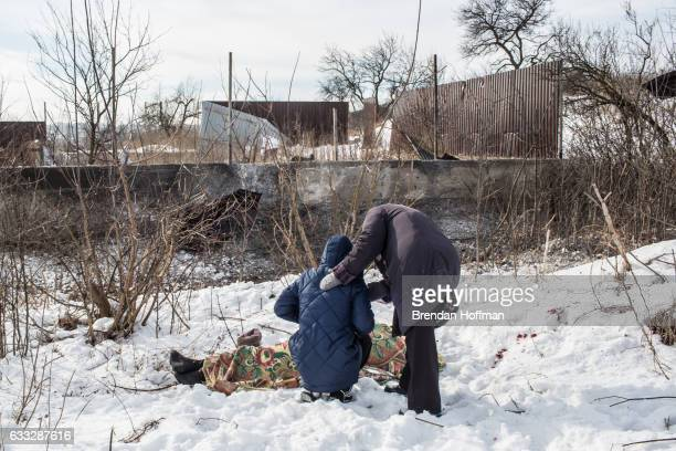 Nadiya Volkova is comforted by her motherinlaw Galina Nikolaevna as she grieves over the body of her mother Katya Volkova who was killed by shelling...