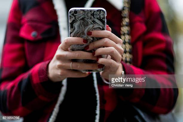 Nadja Ali holding her phone while writting a tex message and having red nail polish wearing a red black plaid lumberjack Levis jacket on November 7...
